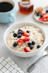 Oatmeal with strawberries and blueberries on grey concrete table background served with cup of black american coffee and raw honey in jar. Healthy breakfast food. Vertical, selective focus