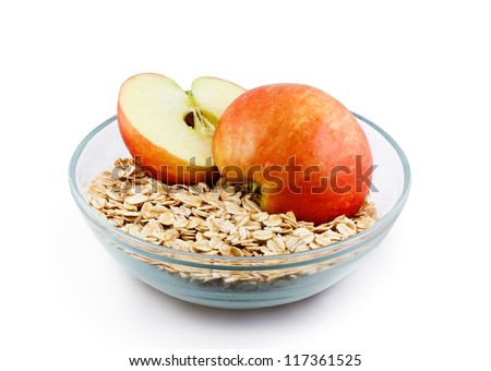 Oats and apple halves in transparent bowl isolated with clipping path