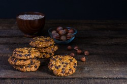 oats cookies with chocolate chips and hazelnuts on a wood table with a bowl of oats flakes and another one of hazelnuts with shell