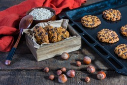 oats cookies with hazelnuts and chocolate chips on a baking sheet, cookies in a box, a spoon and some cloths