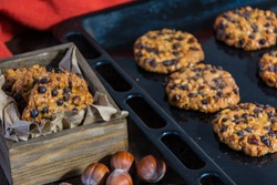 oats cookies with hazelnuts and chocolate chips on a baking sheet, cookies in a box and some cloths