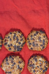 oats cookies with hazelnuts and chocolate chips on a red cloth