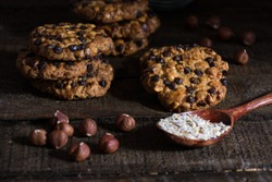 oats cookies with hazelnuts and chocolate flakes on a wood table, and a spoon with oats flakes