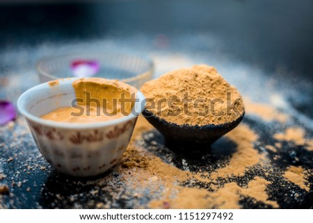 Oats face mask or face pack of Avena sativa i.e. Mulpani mitti or multani mitti or fuller's earth, rose water,lemon juice and powdered oats,on wooden surface.It is used in spa to clean oily skin.