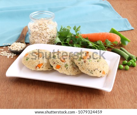 Oats idli or cake, a healthy Indian vegetarian steam-cooked food, with vegetables like carrot and peas,  on a ceramic tray.