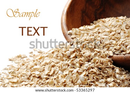 Oats spilling from wooden bowl with white background and copy space.