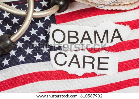 Obama Care in torn paper on American Flag  with stethoscope and
