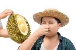 Obese fat boy with expression of disgust against fresh durian isolated on white background, Durian fruit is so smelly and pungent, good taste but bad smell.