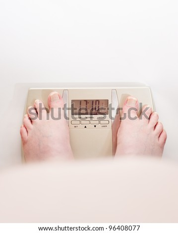 Obese man looking over his fat stomach at his feet on the weighing scales.