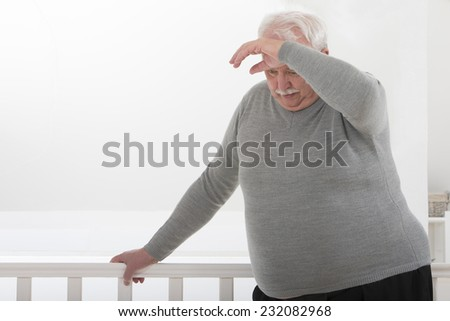 obese man looking worried with hand on forehead