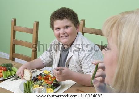 Obese mother and son having meal at home