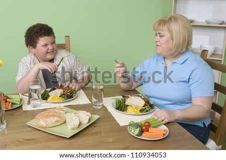 Obese mother and son having meal together at home