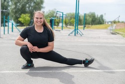 Obese young caucasian woman doing side lunges. Fat beautiful smiling woman in a black tracksuit is engaged in fitness outdoors. Warming up before training.
