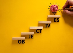Objectives symbol. Wood blocks stacking as step stair on yellow background, copy space. Businessman hand and light bulb. Word 'Objectives'. Business and objectives concept.