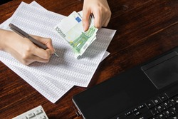 Obligation to pay wages and debts in the company.A cashier holds money Euro over an office work space with documents, a cash register,a phone,and a computer.Work in the office with finances in Europe