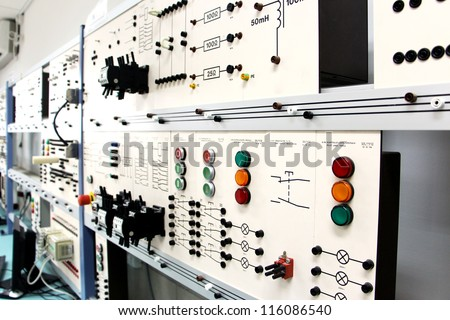 Oblique angle view of a long row of control panels in an electronics lab