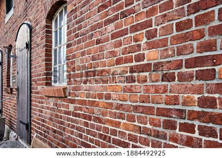 Oblique view of a red old weathered brick wall with a blurred window at the end Foto stock ©