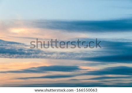 Oblong clouds against evening glow background at sunset