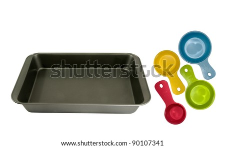 oblong non-stick cake-pan with different measuring cups on a white background