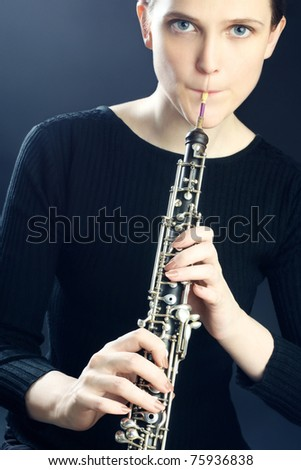 Oboe musical instrument playing. Young oboist musician woman playing classical oboe.