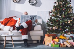 obscured view of santa claus reading business newspaper while sitting on sofa