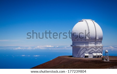 Observatory dome at the peak of Mauna Kea volcano, Hawaii. Telescope structure on volcano top above the main cloud layert.