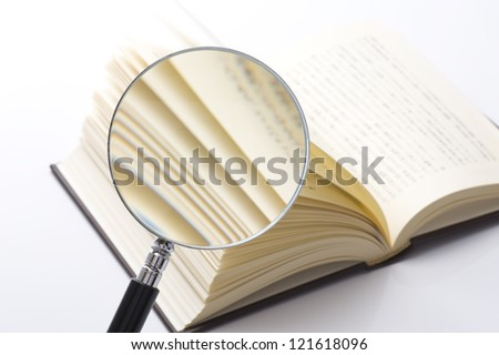 Observed the thick book with a magnifying glass - stock photo