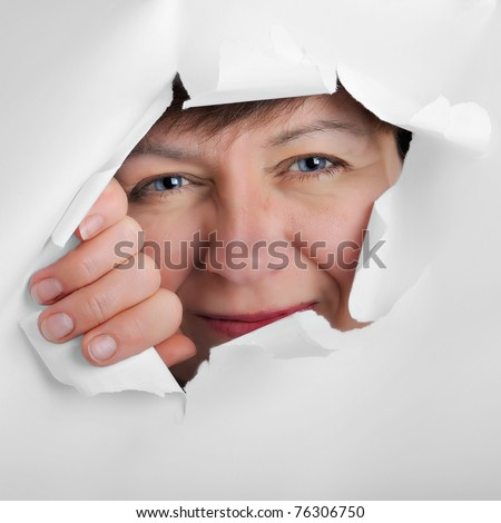 observing eyes of a woman in the hole of white paper