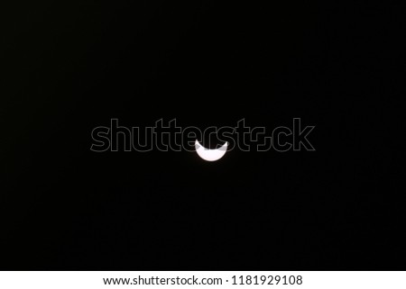 observing with naked eye a partial solar Eclipse, the silhouette of the moon closes the celestial body, the sun went out, a beautiful and rare astronomical phenomenon plunged the world into darkness #1181929108