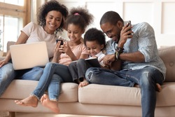 Obsessed to tech devices happy african american family using digital tablet, computer, smartphones. Smiling dad teaching son to use gadgets while mom watching daughter posting in social networks.