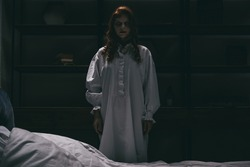 obsessed woman in nightgown standing near bed in dark room