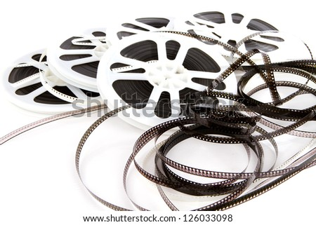 Obsolete rolls of old 8mm movie film are wound on white plastic reels.