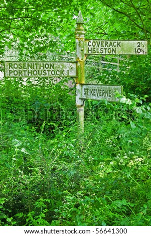 Obsolete signpost ravaged by nature at the side of a disused road in the Cornwall UK