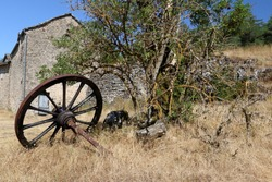 Occitan landscape in France offering a view of an abandoned cart wheel near a tree and a stone house in the background