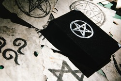Occult grimoire, magic book laying on table with occult symbols, candles, pentagrams, fortune telling, ritual, altar, spiritism, secret knowledge, scull