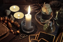 Occulture concept. Burning candles, fortune-telling cards and tincture bottles