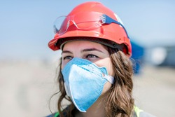 Occupational safety and health specialist (worker, engineer) with face mask for coronavirus (covid-19) in the construction site. Occupational safety and health (OSH).