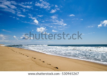 Ocean beach with footprints on sand on background of blue sky