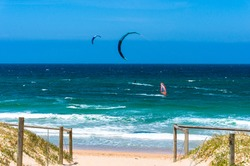 Ocean beach with kite surfers and windsurfers in a distance. Cronulla, Australia
