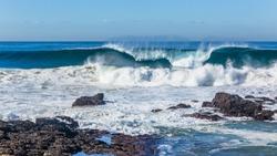 Ocean blues waves crashing breaking crashing water front of rocky coastline.