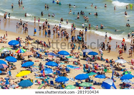 OCEAN CITY - JUNE 14: Crowded beach covered with umbrellas in Ocean City, MD on June 14, 2014. Ocean City, MD is a popular beach resort on the East Coast and one of the cleanest in the country.