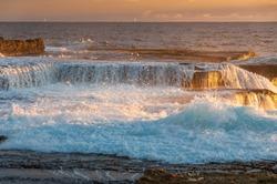 Ocean coastline scene with waves crushing over rocks at sunrise. Sunset, sunrise seascape nature background