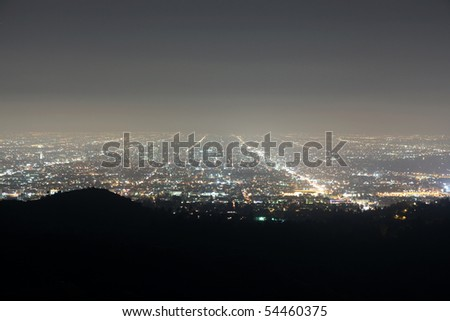 Ocean fog rolls in on the bight lights of Hollywood California. - stock photo
