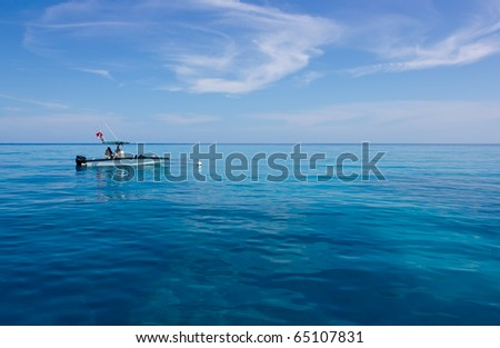 ocean landscape with turquoise water and a lonely boat - stock photo