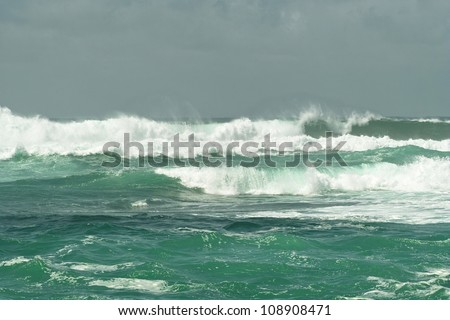 Ocean light green surf waves with white horses near the shore