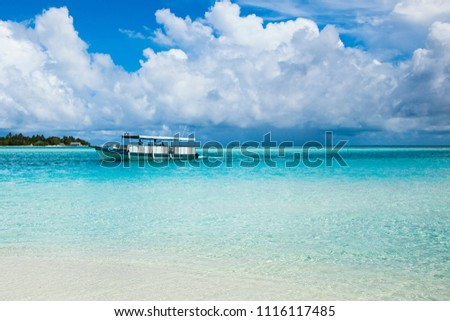 Ocean nirvana. Blue sky and clouds. Boat in blue water. Sandy shore. Maldives Island. Maldive. Summer. May.