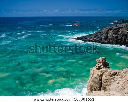Ocean rocky shore and red coastguard boat on green waves.