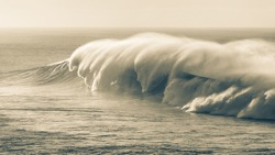 Ocean sea wave breaking crashing with offshore winds spraying water natures power in abstract sepia black white scenic dramatic panoramic  photo.