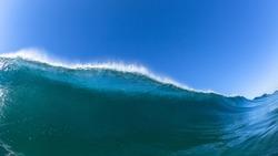 Ocean sea wave encounter swimming closeup water photo of blue water crashing breaking toward beach coastline.