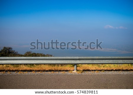 Ocean side highway and gard rail, Behide is beautiful mountain view and blue sky.Road side view mountain and sea background.Side road with mountain and blue sky view #574839811